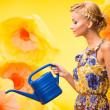 Beautiful young cheerful blond woman in colorful dress among big yellow flowers with watering can — Stock Photo #24040809