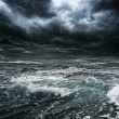 Dark stormy sky over ocean with big waves - Stock Photo
