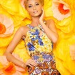 Beautiful young blond woman in colourful dress lying among big yellow flowers — Stock Photo