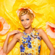 Beautiful young blond woman in colourful dress lying among big yellow flowers — Stock Photo #24040927