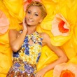 Beautiful young blond woman in colourful dress lying among big yellow flowers — Stock Photo #24040957