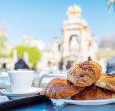 Tasty croissants with cup of coffee against famous fountain view in Barcelona — Stock Photo