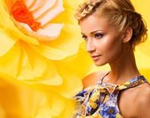 Beautiful young cheerful blond woman in colourful dress among big yellow flowers — Stock Photo