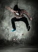 Young man in hat and shirt performing stunt on skateboard — Stock Photo