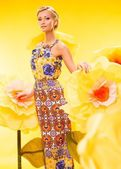 Beautiful young blond woman in colourful dress among big yellow flowers — Stock Photo