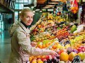 Young cheerful blond woman choosing fresh fruits on market — Stock Photo