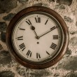 Vintage wooden wall clock on stone wall — Stock fotografie