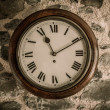 Vintage wooden wall clock on stone wall — Stock Photo #25852095