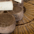 Pieces of tasty cheese on wicker basket — Stock Photo