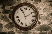Vintage wooden wall clock on stone wall — Stock Photo