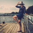 Stylish woman in white hat standing on old wooden pier — Stock Photo
