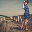 Stylish woman in white hat standing on old wooden pier — Stock Photo #26309127