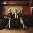 Handsome brunette on sofa with two beautiful women  — Stok fotoğraf