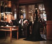 Elegant couple in formal dress in luxury cabinet — Stock Photo