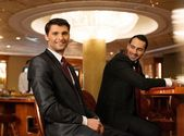 Two young men in suits behind table in a casino — Foto Stock