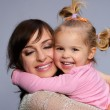 Mother holding her daughter — Stock Photo #27562325