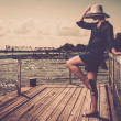 Fashionable woman on an old pier — Stock Photo #27562507