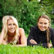 Two beautiful smiling girls lying on a grass in a park  — Stock Photo