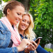 Two beautiful smiling young girl in jeans jackets with cell phone sitting on a bench in a park — Stock Photo #28673511