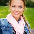 Beautiful young woman in a blue jacket and pink scarf sitting on a bench in a park — Stock Photo