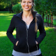 Young beautiful sporty brunette woman in a park with earphones — Stock Photo