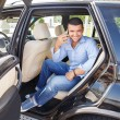 Handsome stylish man on a back seat with a mobile phone — Stock Photo #28673565