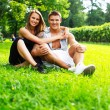 Young happy smiling sporty couple sitting on a meadow in a park — Stock Photo