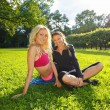 Two smiling athletic girls sitting on a grass in a park — Stock Photo