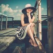 Beautiful woman wearing hat and white scarf sitting on old wooden pier  — Stockfoto
