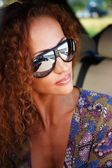 Beautiful middle-aged redhead woman wearing sunglasses in a car — Stock Photo