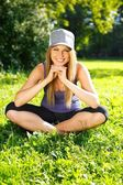 Krásná usměvavá sportovní dívka sedící na trávě v parku — Stock fotografie