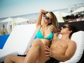 Sexy young couple relaxing on a beach bed — Stock Photo