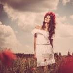 Girl wearing white summer dress and flower chaplet in poppy filed — Stock Photo #29113017