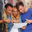 Surprised friends with a tablet pc outdoors — Stock Photo