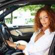 Redhead woman behind steering wheel — Stock Photo
