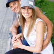 Sporty couple sitting on bench in a park — Foto Stock