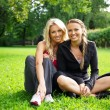 Athletic girls sitting on a grass in a park — Stock Photo