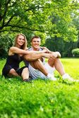Sporty couple sitting on a meadow in a park — Stock fotografie
