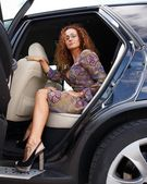 Redhead woman stepping out the car — Stock Photo