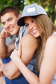 Sporty couple sitting on bench in a park — Stock Photo