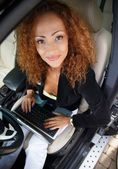 Redhead businesswoman in black jacket with laptop behind steering wheel — Stock Photo