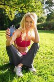 Girl sitting on grass in a park with smartphone and earphones — Stock Photo