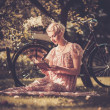 Stock Photo: Retro womreading book on meadow