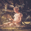 Photo: Beautiful retro woman reading book on a meadow