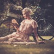 Photo: Retro woman reading book on a meadow