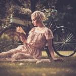 Retro mujer leyendo el libro en un prado — Foto de Stock