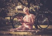 Retro woman reading book on a meadow — Stok fotoğraf