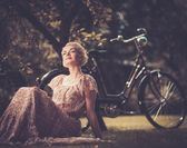 Retro woman in summer dress sitting on a meadow — Stockfoto