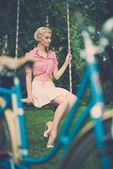 Retro woman sitting on a swings outdoor — Stock fotografie
