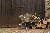 Wheelbarrow with logs standing — Stock Photo